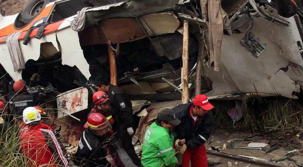 Rescue workers carry a body from a crashed bus after it ran off the highway in La Delicia, Ecuador
