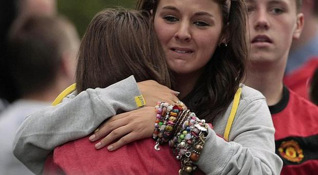 Young people gather at the scene where a missing 12-year-old girl was found dead