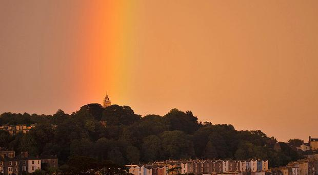 A spectacular storm over the city of Bristol causes a rainbow to form against a dramatic pink sky at the start of the Bank Holiday weekend