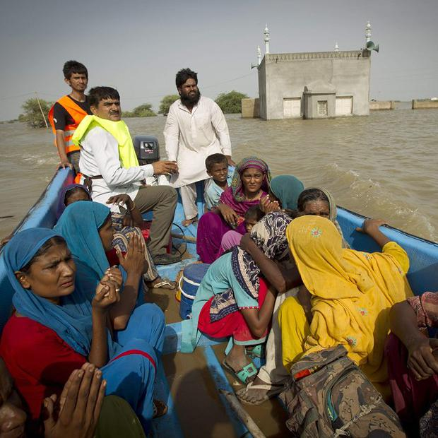Pakistani families are evacuated by boat after their home was totally surrounded by flood waters near Thatta (AP)