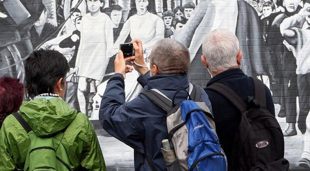 Tourists photograph murals on the Falls Road in Belfast