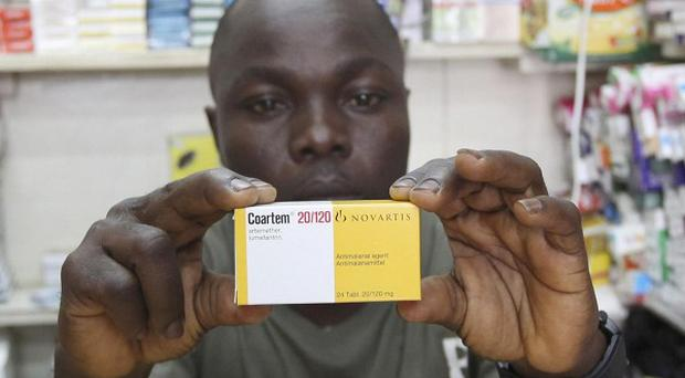 Ayo Bello displays a box of Coartem malaria medication, packaged for the commercial market, at a pharmacy in Lagos, Nigeria (AP)