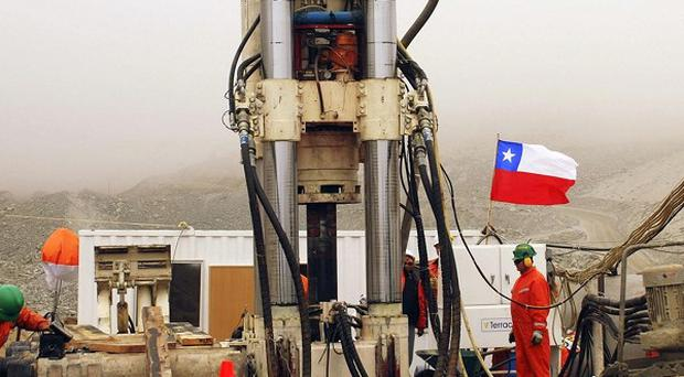Men work on a new drill to be used in the rescue of 33 miners from the San Jose mine in Copiapo, Chile