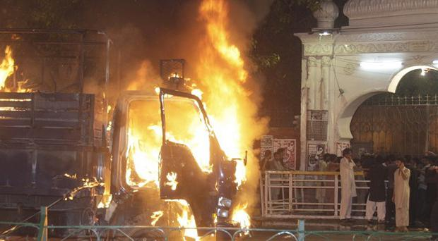 Angry protesters burned a police vehicle after three bombings in Lahore, Pakistan