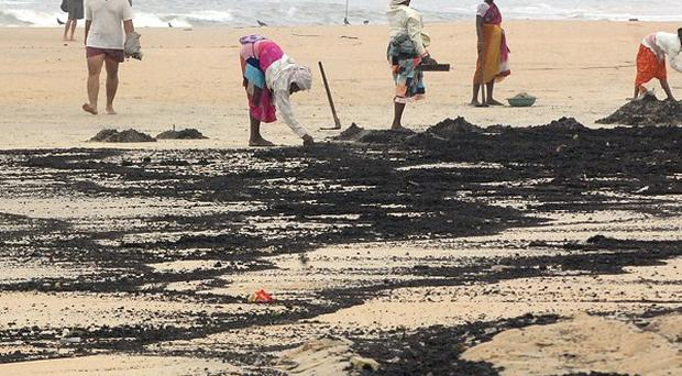 Workers clear tar balls from Colva beach in Goa, India