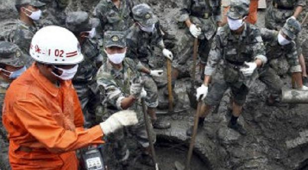 Rescuers search for people missing after a landslide in the village of Wama, Yunnan, south-west China