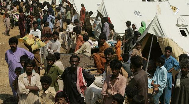 Flood victims wait for food at a relief camp in Thatta, northern Pakistan
