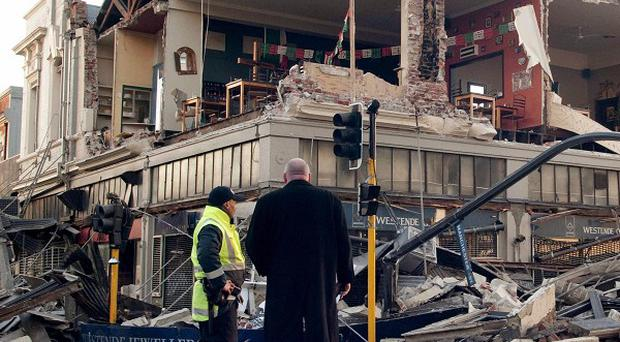 People stand outside a building damaged by a 7.4-magnitude earthquake in central Christchurch