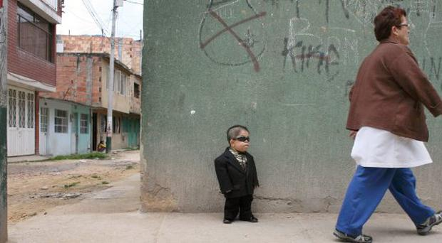Edward Nino Hernandez, 24, waits outside his home for a ride that will take him to a store where he works as a performer in Bogota, Colombia, Sunday Sept. 5, 2010.