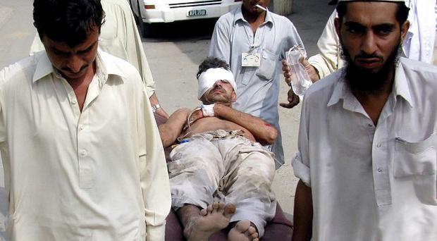 Volunteers and hospital staff carry an injured victim of the Pakistan suicide bombing to hospital