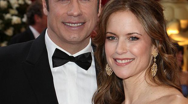 Charges against two people accused of trying to extort money from John Travolta were dropped