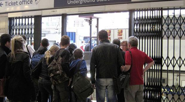 Commuters gather outside an entrance to Victoria Tube station amid a strike by Underground workers