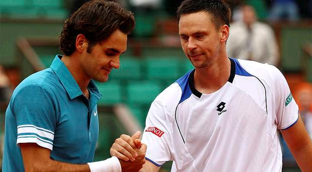 Roger Federer shakes hands with Robin Soderling after the Swede's shock win in Paris