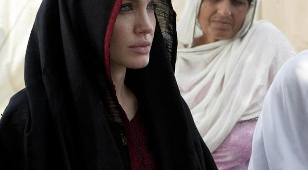 Angelina Jolie, left, speaks with Pakistani women displaced by heavy floods in the country (AP)