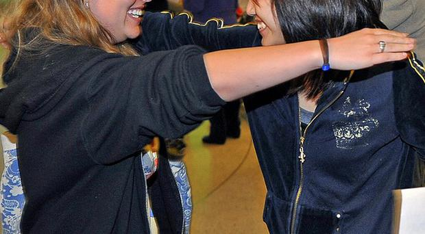 Passenger Thitikarn Tangthanasup, right, is greeted with a hug from a friend after finally arrived in LA following a bomb threat on her flight (AP)