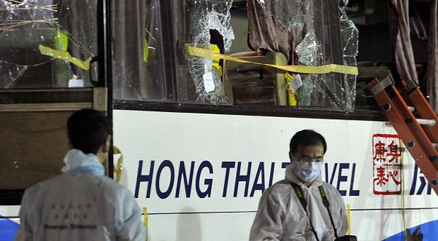 Members of a Hong Kong police forensic team examine the bus used in the hostage-hijacking by an ex-policeman (AP)