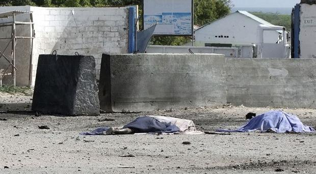 Two bodies lie in front of the Mogadishu airport gate after a suicide bomb and gun attack (AP)