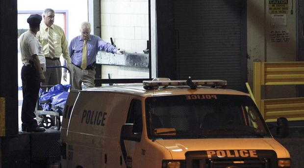 Police remove bodies from the scene of a shooting at the Kraft Foods facility in Philadelphia (AP)