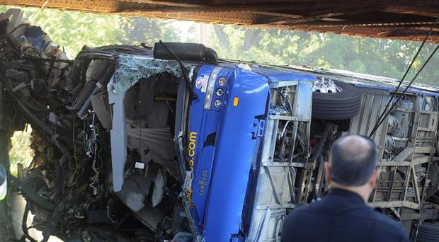 A double-decker bus hit a low railroad bridge and flipped on its side, killing four people and critically injuring others (AP)