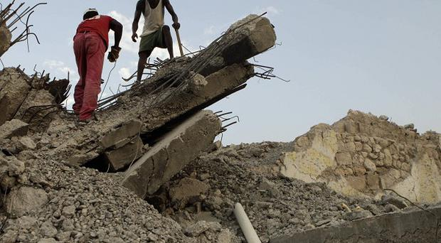 Two men remove rubble from a building destroyed by the January 12, 2010 earthquake in Port-au-Prince, Haiti