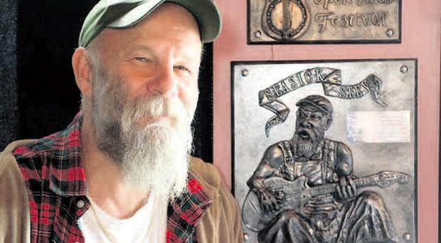 Welcome back: Seasick Steve is presented with a commemorative plaque at Belfast's John Hewitt pub ahead of his performance for the Open House Festival last night. Festival director, Kieran Gilmore, presented the plaque to commemorate the musician's debut solo performance at the festival in 2005