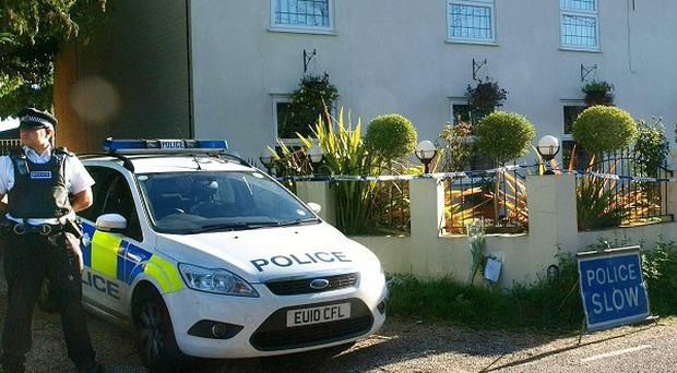 A policeman stands guard outside the house where Margaret Pierides, 16, and her father Costas Pierides, 48, were found
