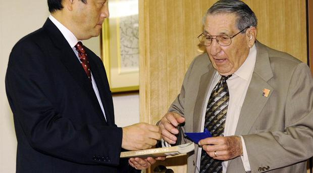 Lester Tenny, right, a former US prisoner of war gives a copy of his book to Japanese Foreign Minister Katsuya Okada