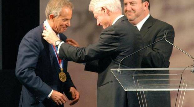 Former US President Bill Clinton (C), along with National Constitution Center's president David Eisner (R), presents former Prime Minister Tony Blair (L) the 2010 Liberty Medal at the National Constitution Center September 13, 2010 in Philadelphia