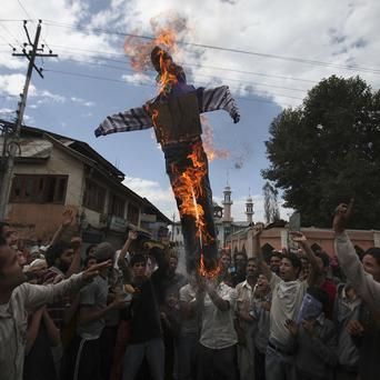Kashmiri protesters lift and burn an effigy of US President Barack Obama during a protest in Srinagar, India (AP)