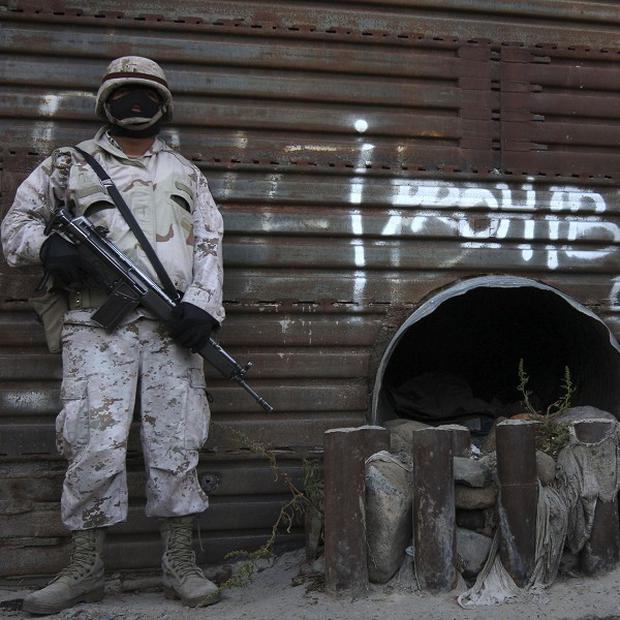 Mexican army soldiers stand guard next to a tunnel at the border wall in Tijuana, Mexico (AP)