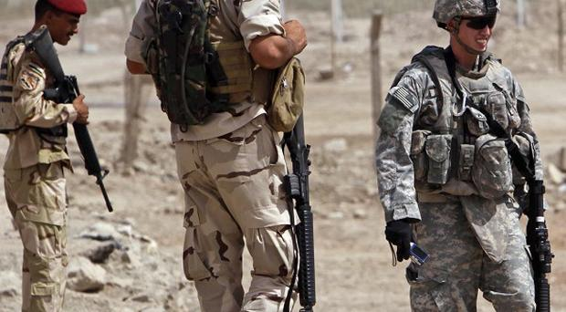 A US soldier and Iraqi security forces inspect the scene of the roadside bomb attack (AP)