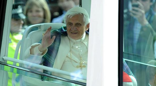 Pope Benedict XVI rides in the Popemobile down Edinburgh's Princes Street