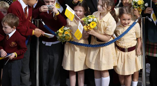 Children wait to greet Pope Benedict XVI as he arrives at St Mary's University College during day two of his four day state visit to the United Kingdom at Twickenham