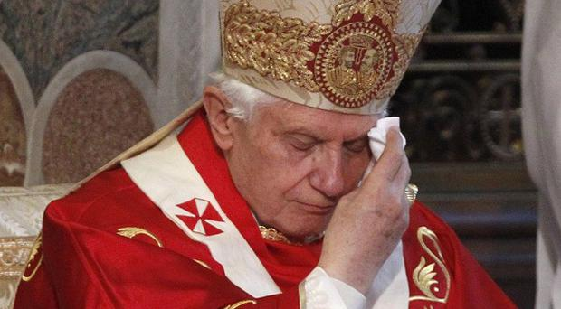 Pope Benedict XVI wipes his brown as he presides over a Mass at Westminster Cathedral in central London