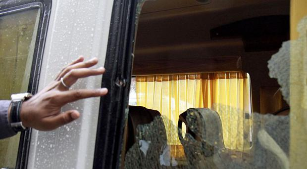 An Indian official inspects the shattered window of a bus attacked by gunmen near Jama Masjid mosque in New Delhi. (AP)