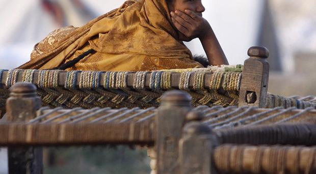 A Pakistani floods survivor lies on a rope bed while waiting for relief goods (AP)