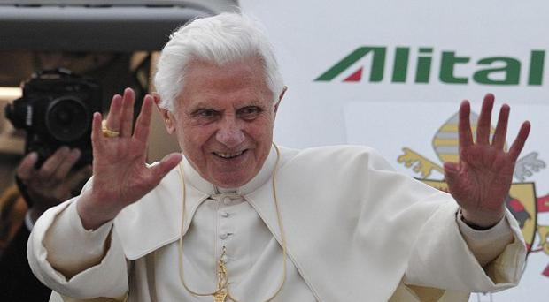 Pope Benedict XVI waves as he boards his aircraft at Birmingham International Airport on the last day of his UK visit