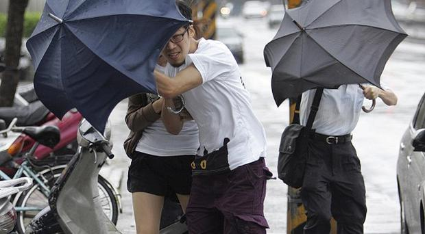 People struggle against powerful gusts of wind generated by typhoon Fanapi in Taipei, Taiwan