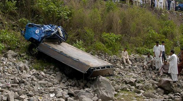 Local residents watch as the damaged vehicle is pulled from the river (AP)