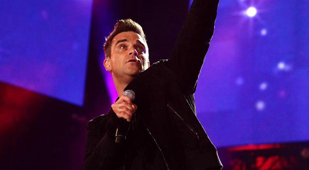 Robbie Williams has admitted he laughed when Kylie stripped off