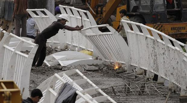 Indian workers remove debris of the collapsed bridge near Jawaharlal Nehru stadium in New Delhi