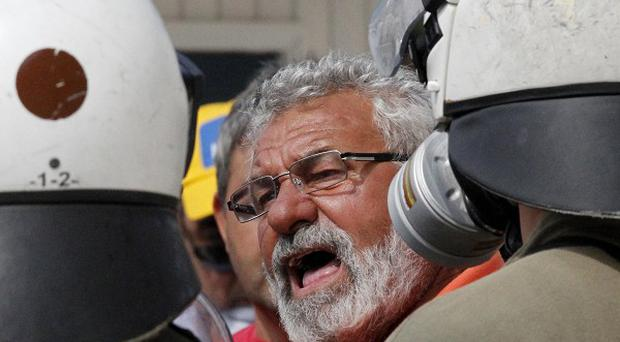 A truck driver argues with riot police outside the Greek Parliament in Athens (AP)