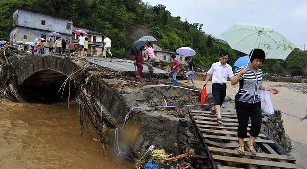 People walk across a flood-damaged bridge in Qianpai Town in Xinyi, south China's Guangdong Province (AP)