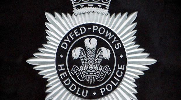 Dyfed Powys have taken a 13-year-old boy into custody after he allegedly shot his teacher in the face