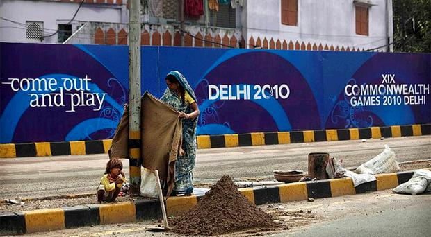The child of a labourer looks on yesterday, as a woman works in the backdrop of a banner for the Commonwealth Games which is expected to go ahead despite the poor facilities and infrastructure in New Delhi