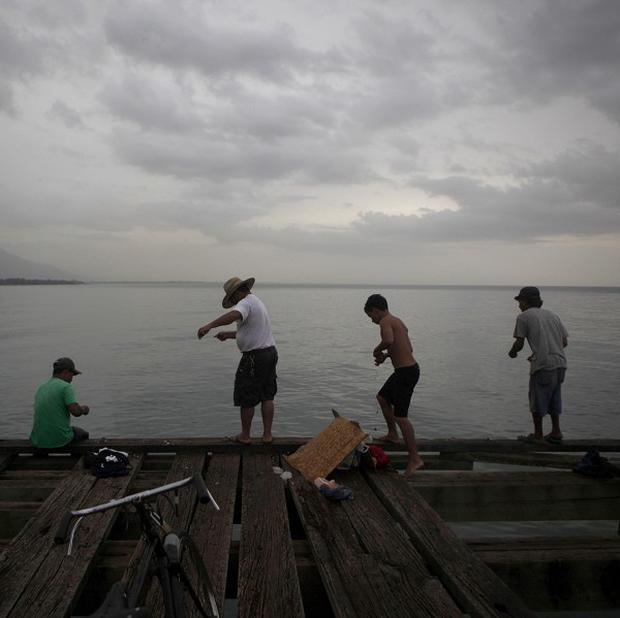 Men fish before heavy rain in La Ceiba, Honduras, as Tropical Storm Matthew drenched the Caribbean coast (AP)