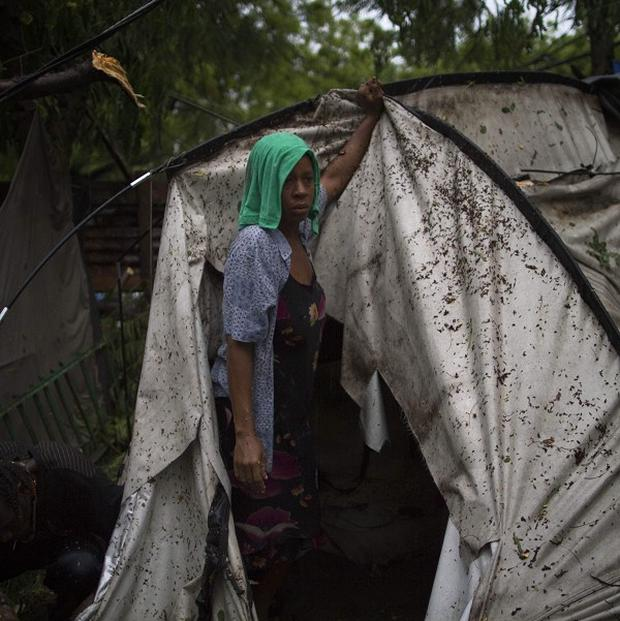 An earthquake survivor tries to set up her tent after it fell down due to heavy rain in Port-au-Prince, Haiti (AP)