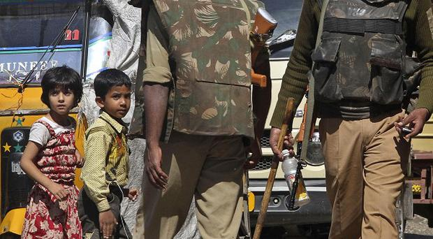 Kashmiri children look at paramilitary soldiers urging civilians to stay indoors during curfew in Srinagar, India (AP)