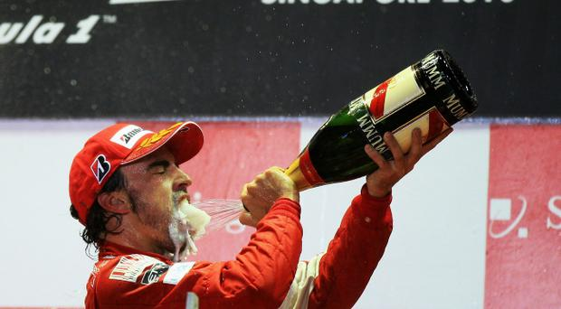 SINGAPORE - SEPTEMBER 26: Fernando Alonso of Spain and Ferrari celebrates on the podium after winning the Singapore Formula One Grand Prix at the Marina Bay Street Circuit on September 26, 2010 in Singapore. (Photo by Mark Thompson/Getty Images) *** BEST PIX ***