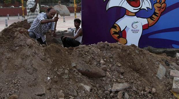Workers repair electrical faults near a portrait of Shera, the Commonwealth Games mascot in New Delhi (AP)